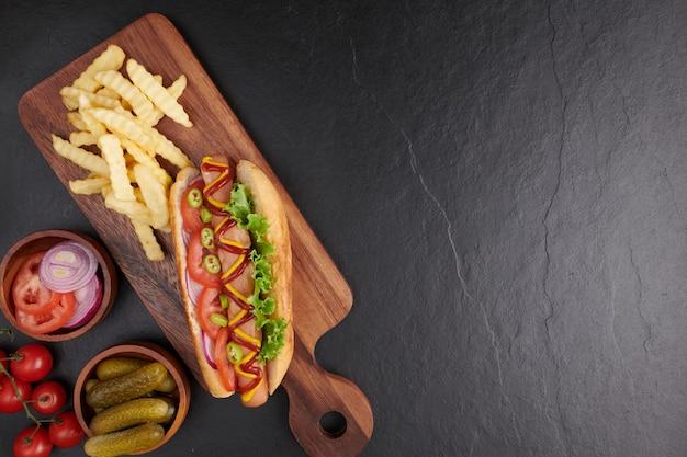 Perrito caliente de ternera a la parrilla gourmet con acompañamientos y papas fritas. deliciosos y sencillos hot dogs con mostaza, pimiento, cebolla y nachos. perritos calientes completamente cargados con ingredientes variados en una tabla de remo.