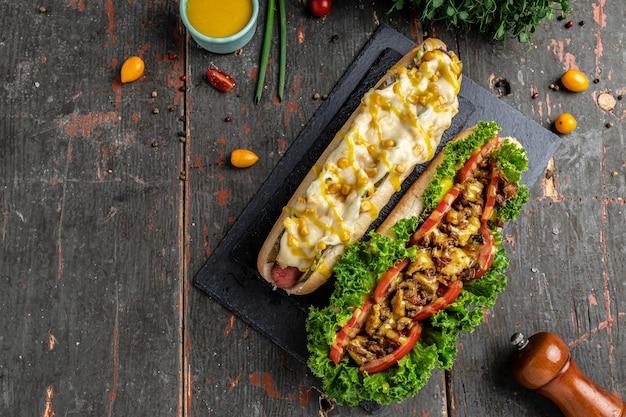 Perritos calientes completamente cargados con ingredientes variados. hotdog de comida rápida, comida estadounidense de calorías poco saludables. banner, menú, lugar de receta para texto, vista superior.