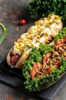 Perritos calientes completamente cargados con ingredientes variados. hotdog de comida rápida, comida rápida y concepto de comida chatarra. imagen vertical. vista superior. lugar para el texto