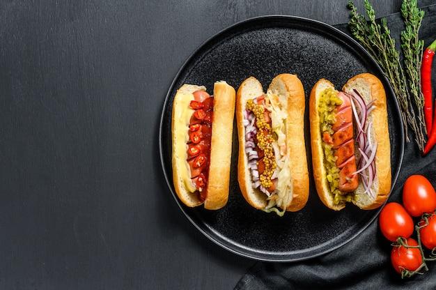 Perritos calientes completamente cargados con una variedad de ingredientes en una bandeja. deliciosos hot-dogs con salchichas de cerdo y ternera. fondo negro. vista superior. copia espacio