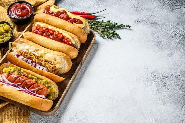 Perritos calientes completamente cargados con una variedad de ingredientes en una bandeja.
