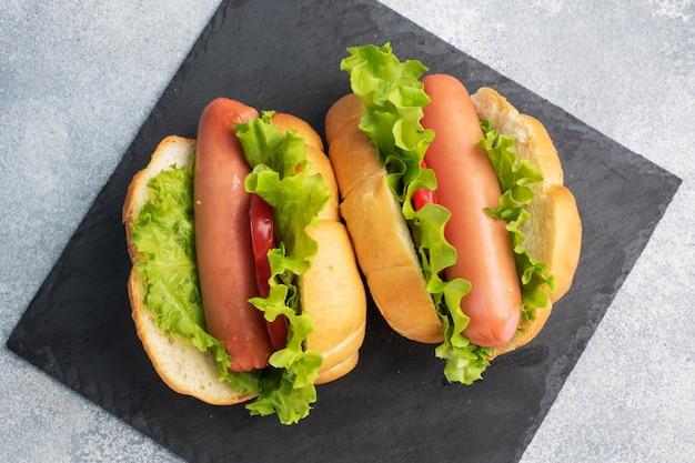 Perritos calientes en un fondo gris concreto. hot dog con lechuga tomate y salchicha. copia espacio