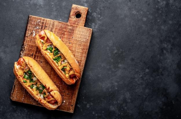 Perritos calientes franceses al horno con queso y mostaza sobre un fondo de piedra