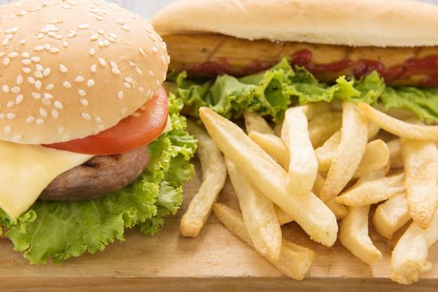 Perritos calientes, hamburguesas y papas fritas en la mesa de madera.