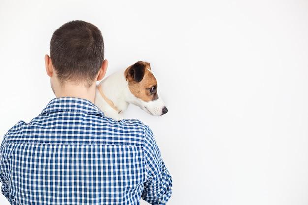 El perro se acuesta sobre el hombro de su dueño. jack russell terrier en manos de su dueño