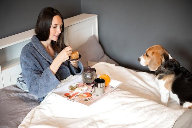 Perro beagle viendo a una mujer desayunar pastel en el dormitorio de la casa