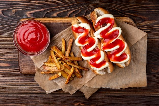 Perro caliente con mayonesa y salsa de tomate y papas fritas sobre fondo de madera oscura.