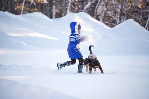 Perro feliz y una niña alegre corriendo en un campo nevado cerca del bosque en un día soleado de invierno.