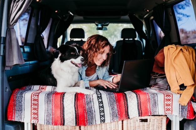 Perro de la mujer y del border collie en una furgoneta. mujer que trabaja en la computadora portátil. concepto de viaje