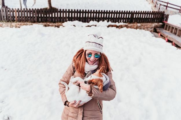 Perro de la mujer y de jack russell que juega al aire libre en la montaña. temporada de invierno