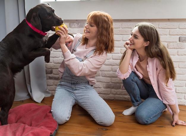 Perro y mujeres felices de tiro completo