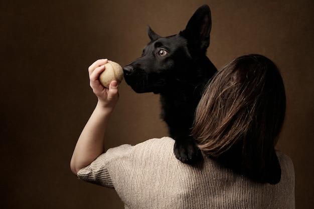 Perro pastor alemán negro y con el dueño de la niña
