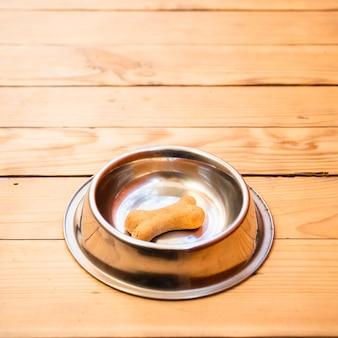 Perro y plato de comida con hueso