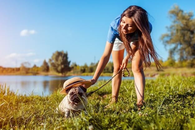 Perro pug sentado junto al río mientras la mujer le pone el sombrero. feliz cachorro y su maestro caminando y relajándose al aire libre