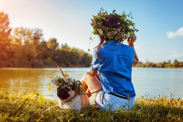 Perro pug y su maestro relajarse junto al río con coronas de flores. feliz cachorro y mujer disfrutando de la naturaleza de verano al aire libre