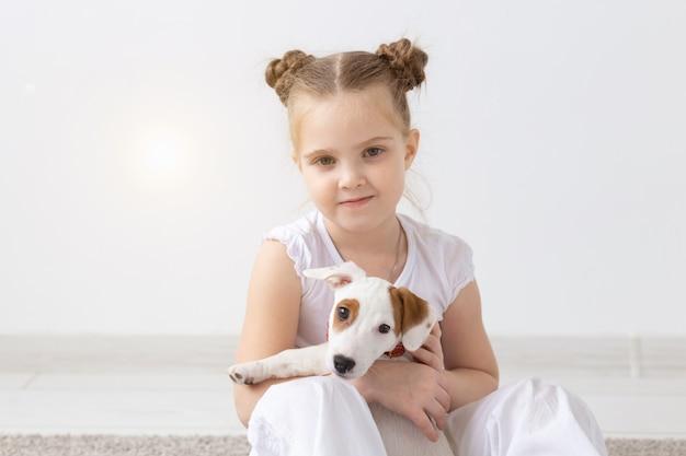 Perros mascotas y concepto animal niña niño sentado con cachorro jack russell terrier