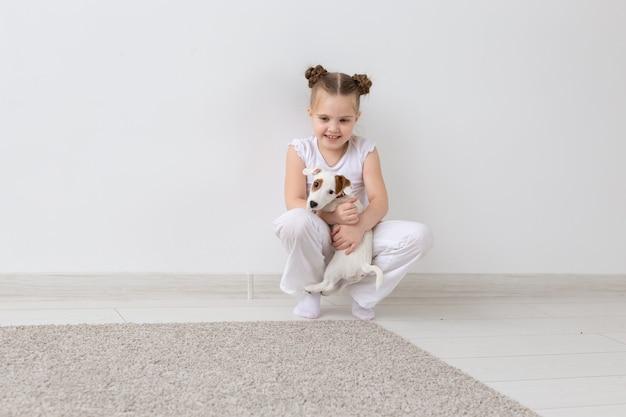 Perros, mascotas y concepto de animales - niña pequeña sentada con cachorro jack russell terrier.