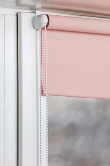 Persiana enrollable de color en la ventana de plástico blanco. persianas en la ventana de plástico.