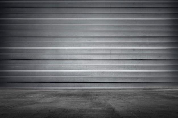 Persiana metálica enrollable de textura con piso de concreto.
