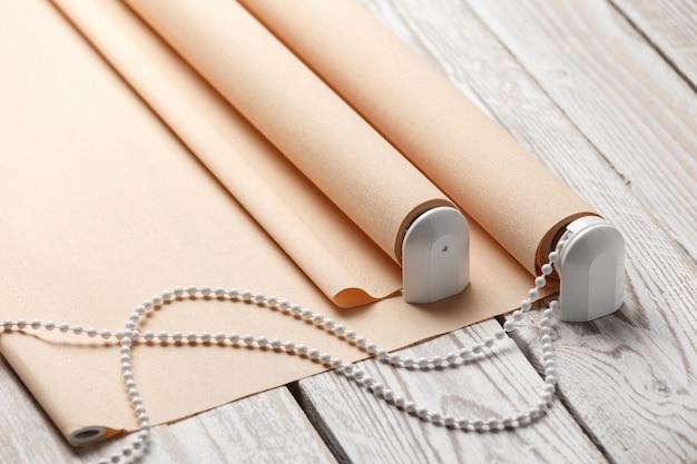 Las persianas beige enrolladas están sobre una superficie de madera. las persianas de color beige se encuentran en una vieja mesa de madera blanca.