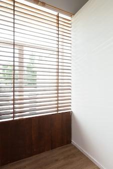 Persianas de madera con luz solar en habitación de casa.