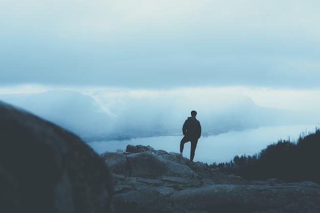 Persona en un abrigo cálido de pie sobre una montaña rocosa y mirando a los árboles