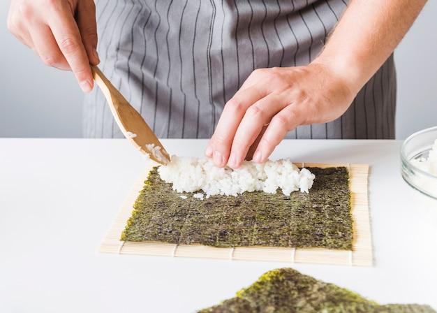 Persona agregando arroz en nori