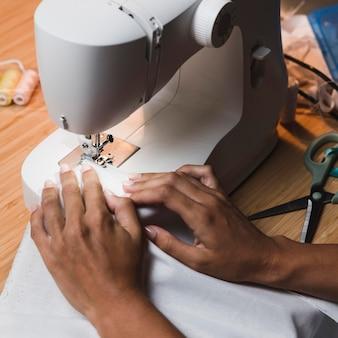 Persona de alta vista cosiendo con una máquina de coser