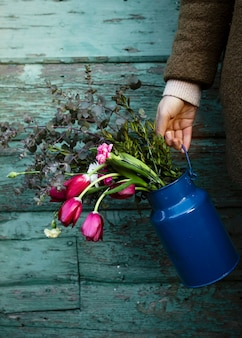 Persona de alto ángulo con jarrón de flores