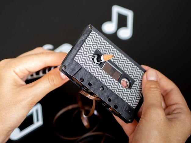 Persona arreglando cinta de cassette rota