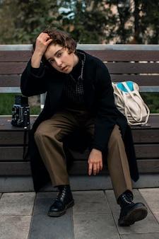 Persona artística no binaria sentada y posando en un banco