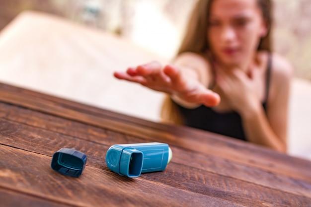 Una persona asmática está tratando de alcanzar el inhalador durante un ataque de asma.