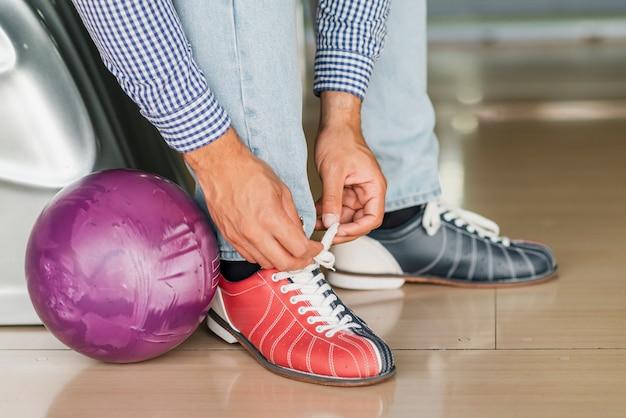 Persona atar cordones de zapatos y bola de boliche