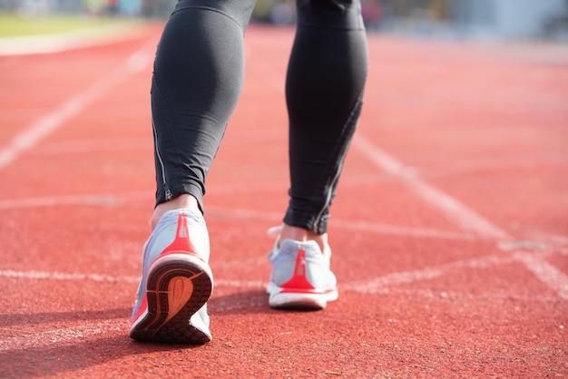 Persona atlética en la pista de atletismo preparándose para comenzar a correr
