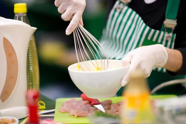 Persona batiendo huevos en un bol