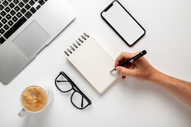 Persona con bolígrafo en mano sobre el bloc de notas