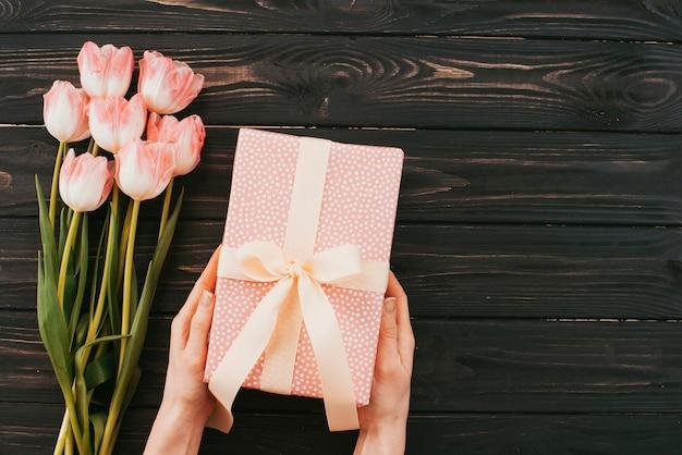 Persona con caja de regalo cerca de ramo de tulipanes