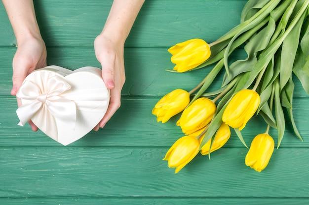 Persona con caja de regalo en forma de corazón cerca de tulipanes