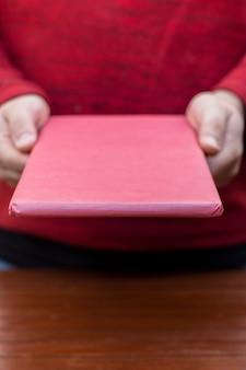Persona con caja de regalo rosa en las manos