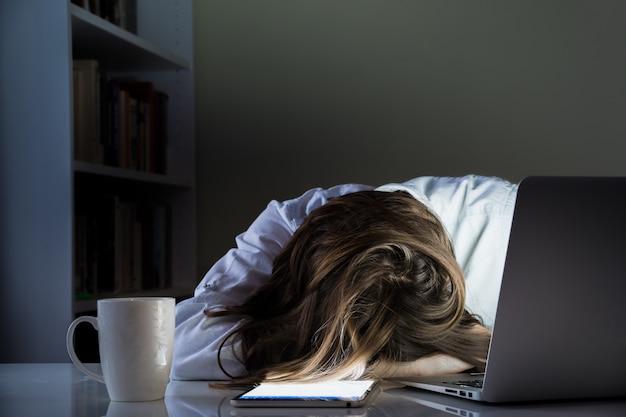 Persona cansada que duerme en el escritorio en la oficina en casa con la computadora y la tableta