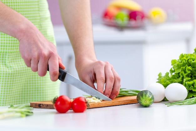 Persona de cocina en delantal cortando productos ecológicos para ensalada de verduras frescas y saludables en la cocina de su casa.