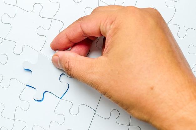 Persona colocando la última pieza del rompecabezas. imagen conceptual del edificio y botón para arriba