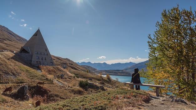 Persona contemplando el paisaje alpino en otoño con lago y montañas