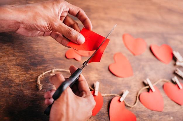 Persona cortando corazones de papel