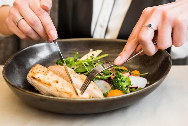 Persona cortando pechuga de pollo gourmet