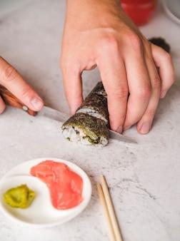 Persona cortando sushi roll close-up