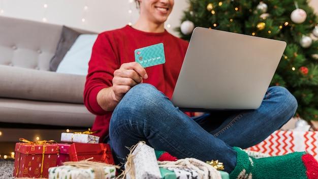 Persona de la cosecha con tarjeta usando laptop para ir de compras