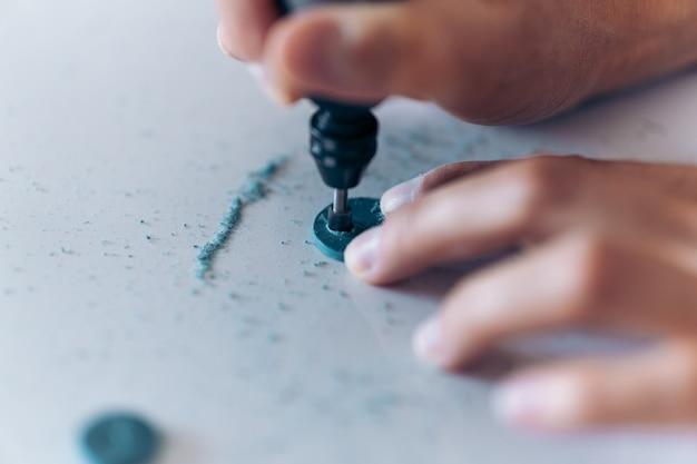 Persona creativa haciendo aretes azules hechos a mano y usando herramientas.