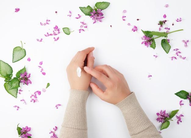 Persona con crema espesa y peonías con flores de color burdeos