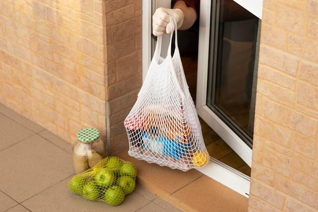 Persona en cuarentena tomando alimentos desde su puerta principal